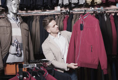 Positive male customer examining coats Stock Photos