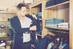 Positive male customer searching new suit. In man clothes store Stock Photos