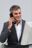 Positive male executive talking on phone. At his desk Royalty Free Stock Photography