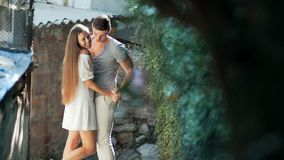 Positive male kissing and hugging cute brunette female on a street in an old town. stock video