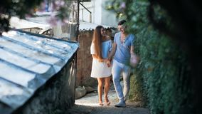 Positive male kissing and hugging cute brunette female on a street in an old town. stock footage