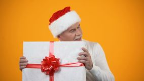 Positive male pensioner in santa claus hat shaking giftbox and smiling, surprise stock video