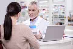 Positive male pharmacist giving advice client Stock Photography