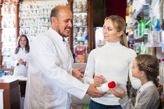 Positive male pharmacist helping customers. Positive male pharmacist wearing white coat standing next to shelves with medicine and helping customers Stock Photos
