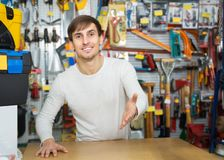 Male seller posing at tooling section. Positive male seller posing at tooling section of household shop Royalty Free Stock Photos