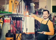 Positive male seller showing assortment in garden equipment shop. Positive male seller showing assortment оf equipment in garden equipment shop stock photography