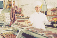 Positive male seller working at meat market Stock Image