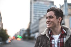 Positive male standing outdoors with joy. Side view of cheerful attractive man walking on street on his own.  He is looking sideways and smiling. Copy space in Royalty Free Stock Images