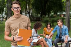 Positive male student relaxing in campus outdoors. Portrait of young smart men in eyeglasses is standing and holding folders with learning material. He is Stock Photos