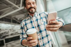 Positive male using mobile during rest. Low angle outgoing bearded man listening music while typing in mobile. He drinking cup of coffee Royalty Free Stock Photos