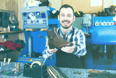 Positive male worker showing fixed shoes. In shoe repair workshop Stock Photos