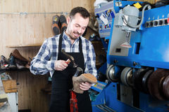 Positive male worker using instruments in workshop. Positive male worker using instruments for fixing in shoe repair workshop Stock Photos