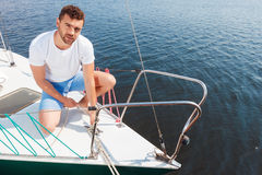Positive man adjusting his yacht Stock Photography