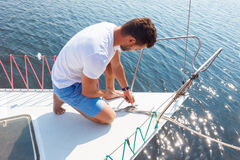 Positive man adjusting his yacht Royalty Free Stock Photos