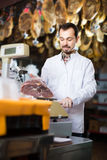 Positive man assistant weighing piece of meat. Positive man assistant weighing on scales piece of meat in butcher's shop Stock Images