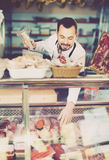 Positive man assistant working with meat Royalty Free Stock Photo