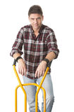 Positive man with cart used for transport Royalty Free Stock Image