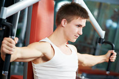 Positive man at chest exercises machine. Smiling fitness man at chest pectoralis woman with training equipmant at fitness club gym doing exercises for back Royalty Free Stock Images
