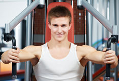Positive man at chest exercises machine. Smiling fitness man at chest pectoralis woman with training equipmant at fitness club gym doing exercises for back Stock Photo