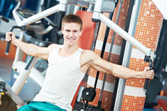 Positive man at chest exercises machine. Smiling fitness man at chest pectoral muscles exercises with training weight machine station in gym Stock Image