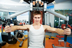 Positive man at chest pectoral exercises machine. Smiling fitness man at chest pectoral muscles exercises with training weight machine station in gym Stock Photos