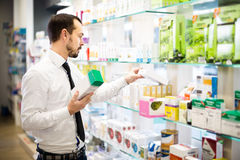 Positive man customer browsing rows of drugs Stock Photography