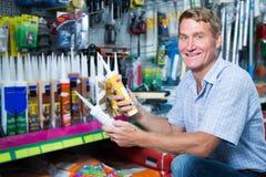 Positive man customer choosing sealant tube in hypermarket Stock Photography