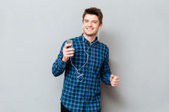 Positive man dancing while listening music on smartphone. Positive man dancing while listening music with headphones on smartphone over grey royalty free stock photos
