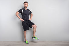 Positive man doing sport exercises. Make it faster. Positive smiling senior man standing  on grey background and doing sport exercises while expressing gladness Royalty Free Stock Photography