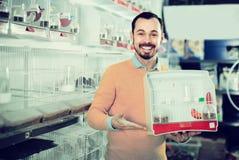 Positive man enjoying his purchase of canary bird Stock Image