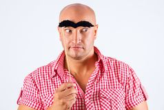 Positive man with false eyebrows, white background with surprised look stock photo