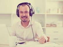 Positive man in headphones near computer Stock Image
