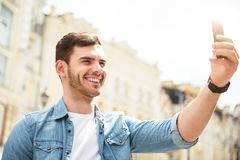 Positive man holding cell phone. Say cheese. Positive handsome smiling man holding cellphone and making selfie while expressing gladness stock photo
