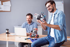 Positive man holding robot Stock Image