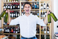 Positive man holding wine bottles in winery section. In store Royalty Free Stock Images