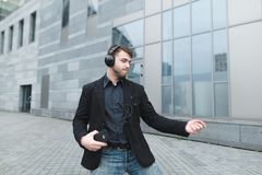 A positive man in a jacket dances to music in headphones against the backdrop of urban landscape. Royalty Free Stock Photos