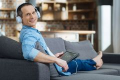 Positive man leaning on sofa. Here I am. Attractive male person keeping smile on his face and turning head while looking straight at camera Royalty Free Stock Photos