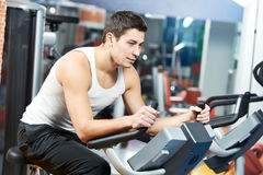 Positive man at legs bicycle exercises machine Stock Image