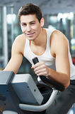 Positive man at legs bicycle exercises machine Royalty Free Stock Images