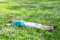 Positive man lying on a green summer meadow. Among wildflowers Stock Image