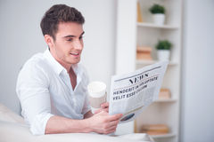 Positive man reading newspaper. Royalty Free Stock Photos