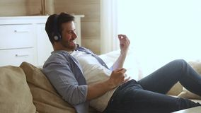 Man wearing headphones resting on couch play on imaginary guitar. Positive man resting on couch spend free time enjoy weekend alone at home wearing headphones stock footage