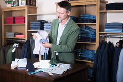 Positive man seller displaying diverse cloths Stock Images