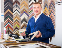 Positive man seller in picture framing studio with wooden detail. Positive man seller standing in picture framing studio with wooden details Royalty Free Stock Photo