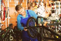 Positive man seller wearing uniform fixing bike. In sport store Stock Photos