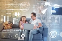 Positive man sitting on the sofa and watching a cartoon with daughter. Funny cartoon. Cheerful emotional young father sitting comfortably on the sofa and holding Stock Photography