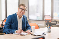 Positive man sitting at the table. Like what you do. Cheerful handsome positive man smiling and making notes while working in the office Royalty Free Stock Photo