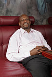 Positive man on sofa. Positive middle-aged african man sitting on red leather sofa Royalty Free Stock Photography