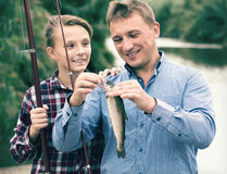 Positive man with son looking at fish on hook Stock Photo