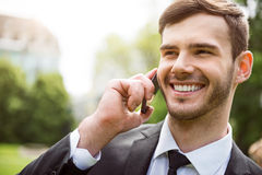 Positive man talking on cell phone. Pleasant call. Portrait of pleasant delighted handsome man holding cell phone and talking on it while expressing gladness stock image